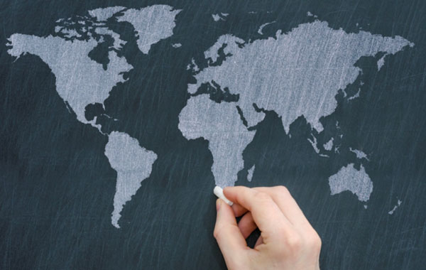 a hand making the finishing touches on Africa on a map of the world drawn on a black chalkboard with white chalk