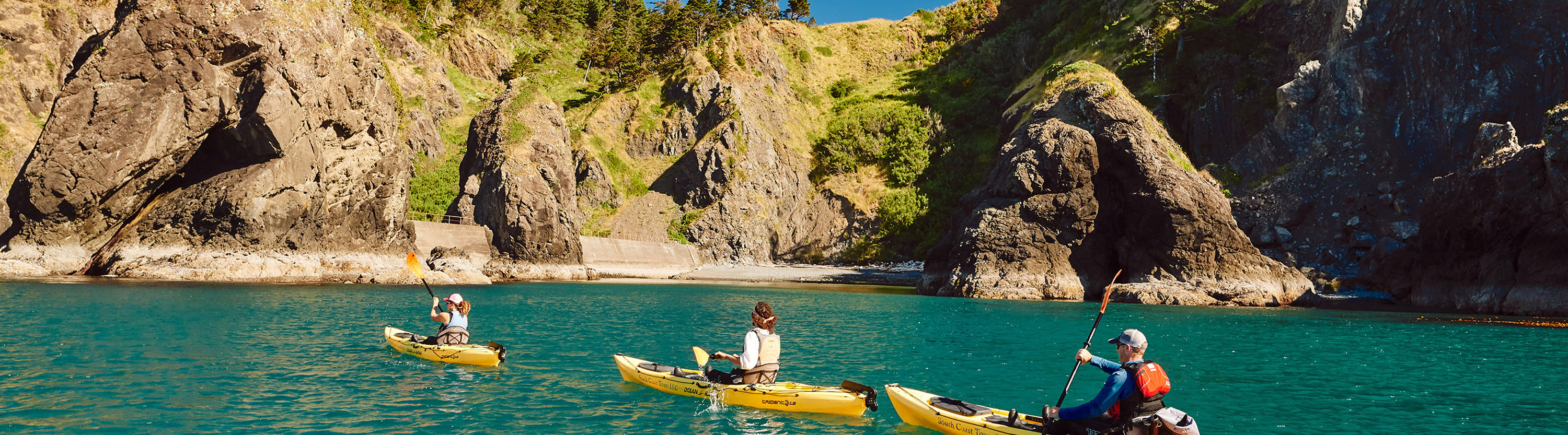 Three people in kayaks on a river between cliffs