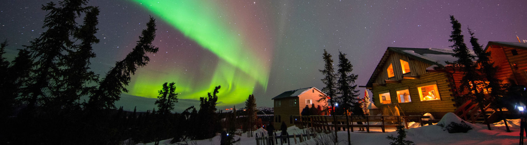 Multiple two story log cabins with people out front gazing at the Northern Lights in the night sky