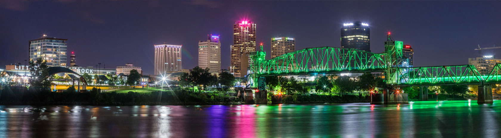 A night shot of the city with the focus on a walkover bridge lit up in green lights in Little Rock, Arkansas