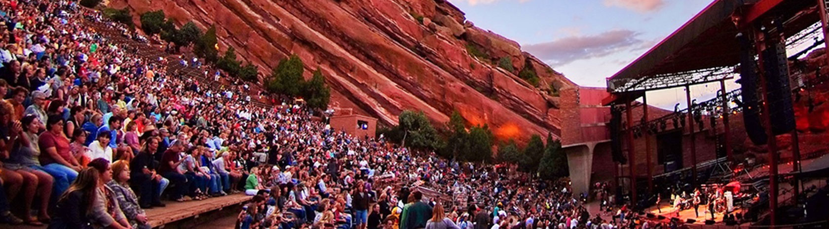 A red rock wall as the side of an arena is the focus with a band playing on the stage with a full crowd in front