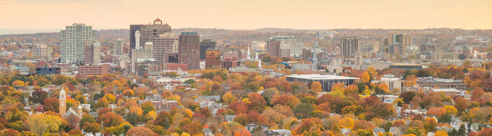A cloud-covered yellow sky over a city with residential homes divided by autumn colored trees in the foreground