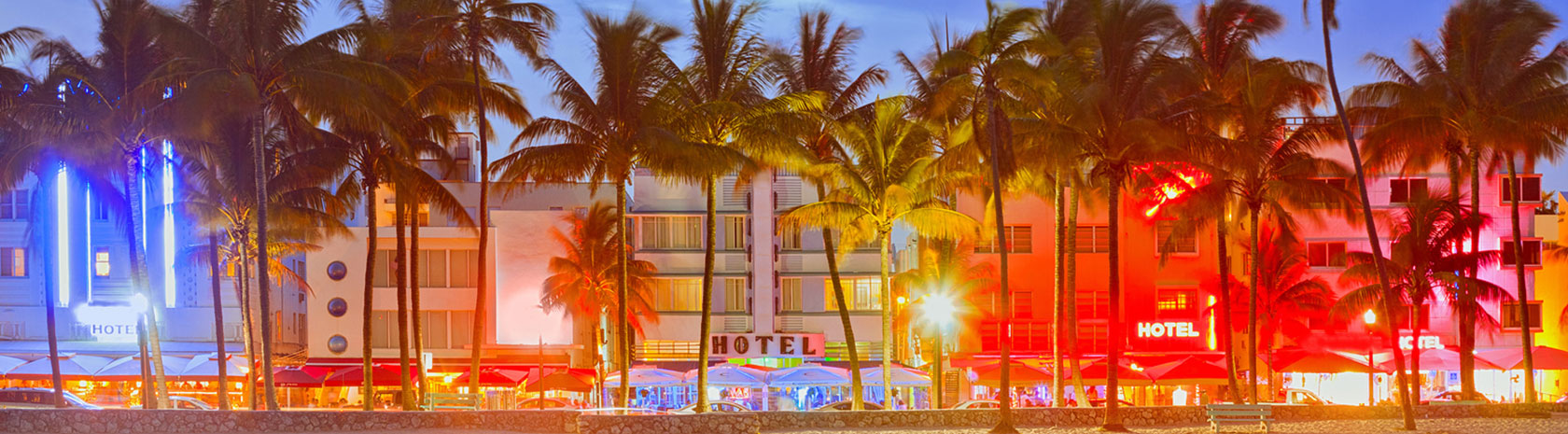A string of 5 hotels, each with different colored lights shining, adjacent to the beach and palm trees in the foreground