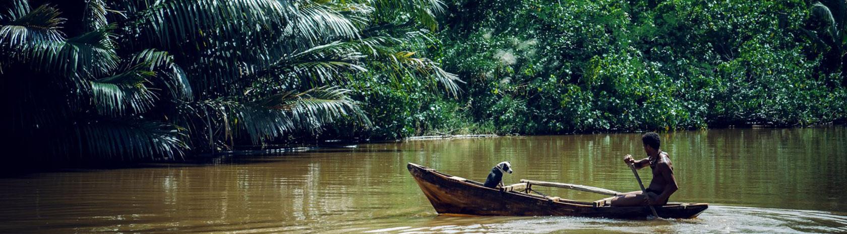 An island native paddles his handmade canoe through a brown river inside of a dense jungle.