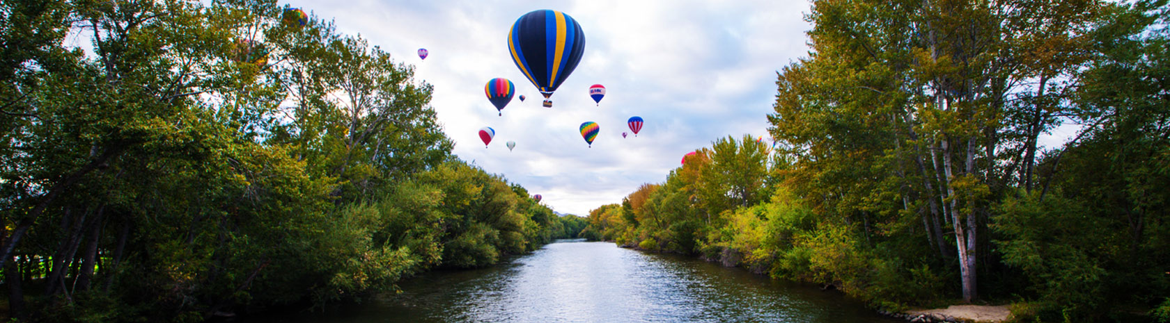 A group of hot air balloons fly over a river with trees on both sides with subtle hints of autumn colors