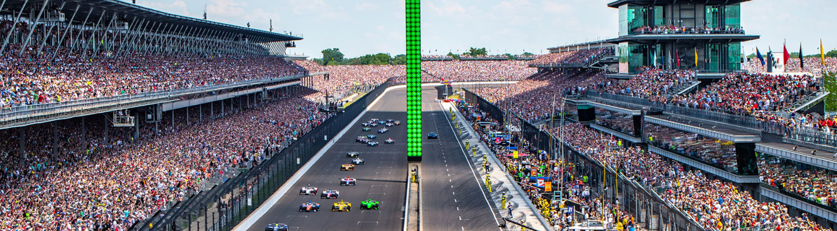 A shot of an indy car race in progress with packed stands