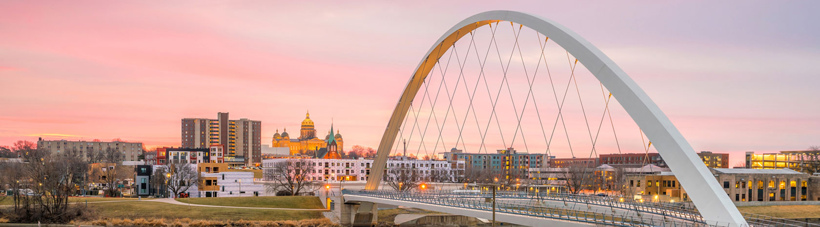 A sunset shot of a single arched bridge with the city buildings in the background