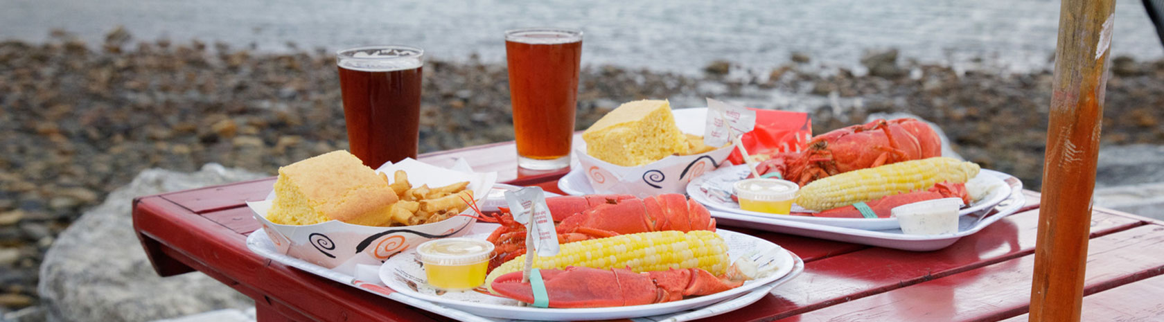 A close up shot of two lobster dishes and beers on a small table with a umbrella on a rocky shoreline.
