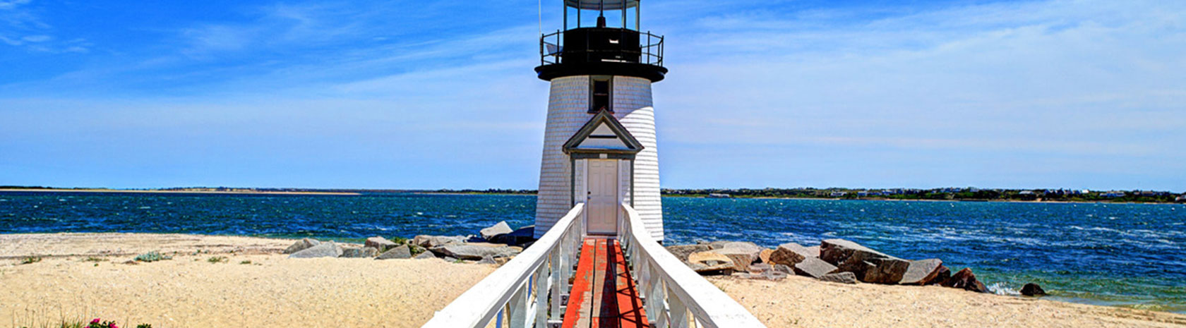 A shorter, white lighthouse sitting on a sandy beach with a wooden, red-floored walkway with white handrails leading up to it.
