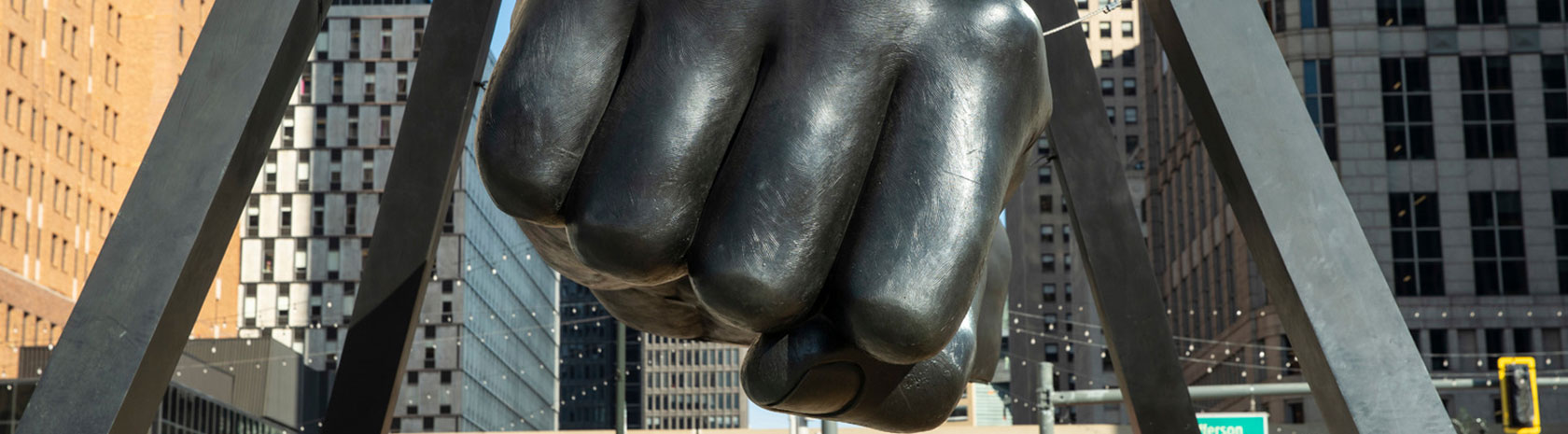 A focus on the giant fist of the Monument to Joe Louis in Detroit; which is a forearm and fist held up by 4 pillars