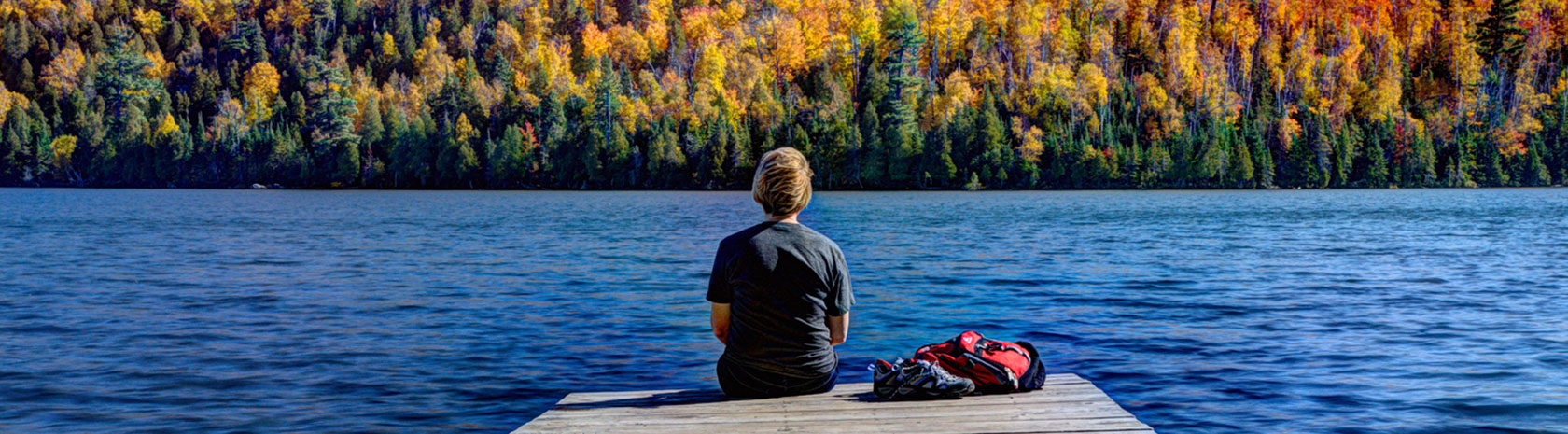 A young man sits at the edge of a pier with his back to the camera staring at the lake and autumn colored trees ahead