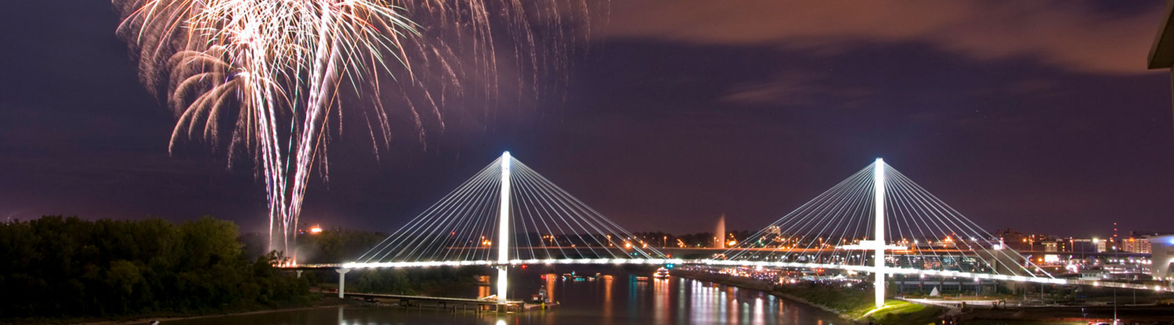 A wide shot of a brightly lit bridge with fireworks firing off from the far end