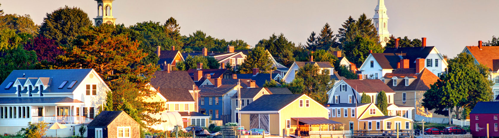 Rooftops and treetops of a tightly packed, small town that is nicely up-kept during early morning