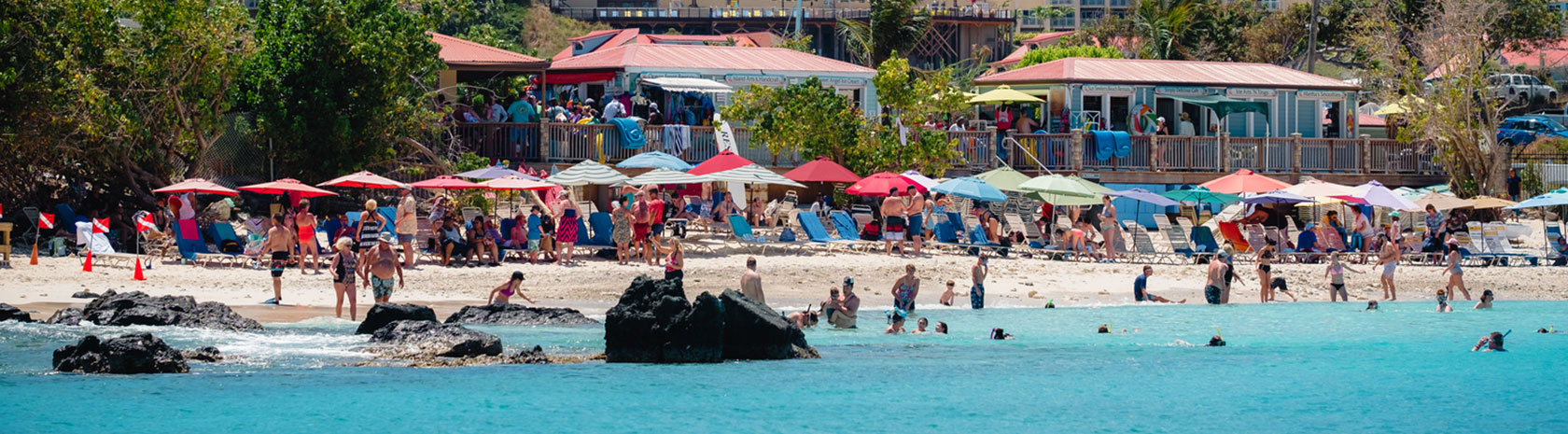 A large crowd of beachgoers enjoying crystal blue waters and beach side businesses