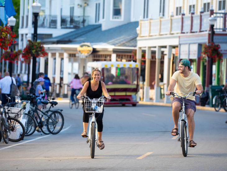 Mackinac Island Couple Biking Down Main Street