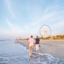 Couple walks along the shores of Myrtle Beach with the board walk, including the ferris wheel, in the background view