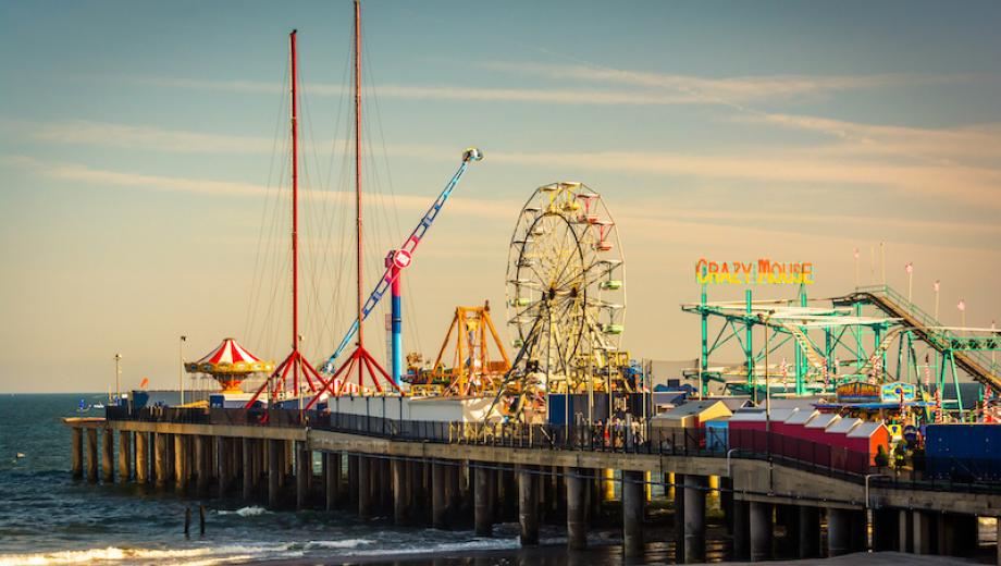 View of Atlantic City, New Jersey pier with amusement park rides at sunset