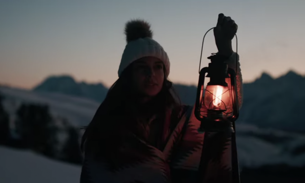 girl holding a lantern at night in the winter