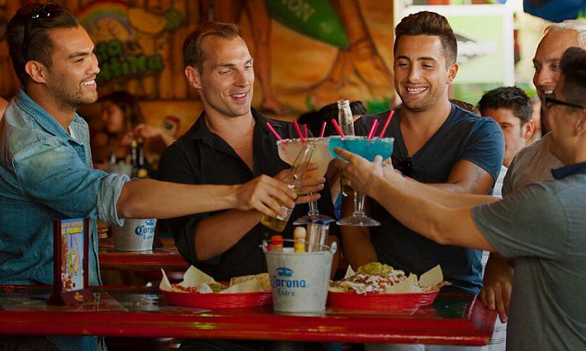 Men cheers their drinks at bar