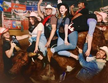 a group of 7 on a mechanical bull, all wearing cowboy clothing