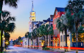 A street in downtown Charleston, South Carolina at sunset with a view of a church steeple
