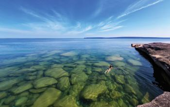 Woman swimming in the crystal clear waters of a Lake Superior in Michigan