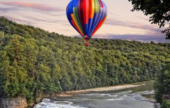 A hot air ballon flies over a waterfall in central New York