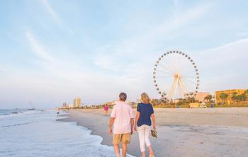 Couple walks along the shores of Myrtle Beach, South Carolina with the board walk, including the ferris wheel, in the background view