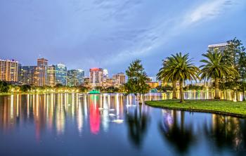 Orlando, FL skyline reflecting over the water at dusk