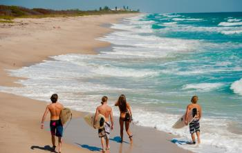 View of surfers walking along the shore of Sebastian's Inlet in Sebastian, Florida