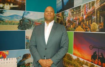 Colin Skerritt posing at the Brand USA booth at IPW 2019